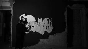 Kunstenaar die witte grafiti met schedel op de zwarte muur schilderen stock footage