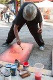 Kunstenaar Flicks Red Paint op het Schilderen bij Kunstenfestival Royalty-vrije Stock Afbeelding