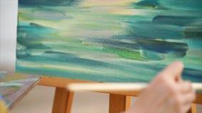 Kunstenaar het schilderen met olie op canvas openlucht stock footage