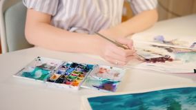 Kunstenaar het schilderen waterverfpenseelstreken sketchbook stock footage