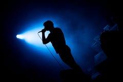 Kunstenaar het zingen in microfoon in stadiumlichten Stock Afbeeldingen