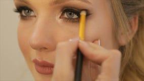 Kunstenaar-merk-op het toepassen van heldere basiskleurenoogschaduw op het oog van een meisje stock video