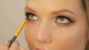 Kunstenaar-merk-op het toepassen van heldere basiskleurenoogschaduw op het oog van een meisje stock videobeelden