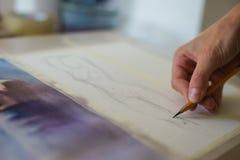 Kunstenaar met een potloodclose-up terwijl het trekken van een schets op schoon document stock afbeelding