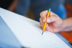 Kunstenaar met een potloodclose-up terwijl het trekken van een schets op schoon document royalty-vrije stock fotografie