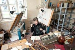 Kunstenaar in onordelijke studio Stock Fotografie