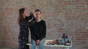 Kunstenaar van de vrouwen vraagt de professionele make-up was op gezicht van jong leuk meisje plastic make-up voor bioskoop aan e stock video