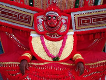 Kunstenaar van oud kunsttheater Kathakali in kostuum en masker: heldere rode brede kleding, slinger van rode bloemen, rood masker Stock Foto