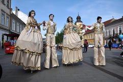 Kunstenaars die op stelten in middeleeuwse kostuums presteren stock fotografie