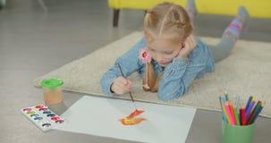 Kunstenaars het aanbiddelijke meisje schilderen op de vloer stock footage