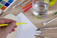 Kunstenaars` s hand op het werk, verven, borstels en potloden Stock Foto's