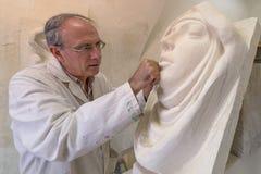 Kunstenaarsmeester aan het werk in studio op een beeldhouwwerk van gezicht Royalty-vrije Stock Afbeeldingen