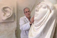 Kunstenaarsmeester aan het werk in studio op een beeldhouwwerk van gezicht Stock Foto