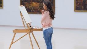 Kunstenaarsmeisje die zich vóór het canvas bevinden steadicam 4K stock video