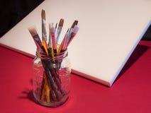Kunstenaarspenselen in metselaarkruik met canvas Stock Afbeeldingen