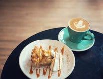 Kunstkaffee des Apfelkuchens und der Schlagsahne und des Latte in der grünen Schale auf schwarzer Tabelle in der Kaffeestube Stockfoto