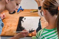 Kunstlehrer, der einem Studenten mit Malerei hilft Stockbilder