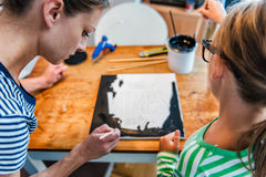 Kunstlehrer, der einem Studenten mit Malerei hilft Stockfotografie