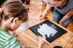 Kunstlehrer, der einem Studenten mit Malerei hilft Lizenzfreie Stockfotografie