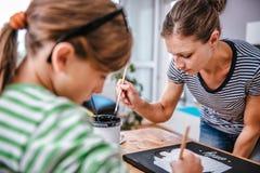 Kunstlehrer, der einem Studenten mit Malerei hilft Lizenzfreie Stockbilder