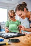 Kunstlehrer, der einem Studenten mit Malerei hilft Stockfotos