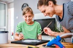 Kunstlehrer, der einem Studenten mit Malerei hilft Lizenzfreie Stockfotos