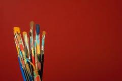 Kunstmalereibürsten mit rotem Hintergrund Stockfoto