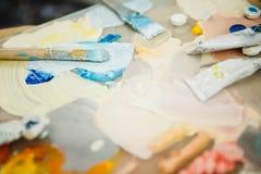Kunstmalereibürsten und -PALETTE auf Hintergrund der Farbe spritzt Lizenzfreie Stockfotos