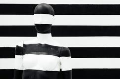 Kunstmannequin-Schwarzweiss-Streifen, auf gestreiftem mit Schwarzweiss-Streifen verkleidung lizenzfreies stockbild