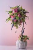 Kunstmatig boeket van diffirent mooie kleine bloemen met aardige zilveren ketting en twee hangende harten bloempot op de achtergr Stock Afbeelding