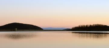 Kunstmatig meer in zonsondergang met bezinning Stock Afbeelding