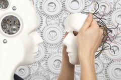 Kunstmatig mensenconcept - de androïde robot houdt kloon wit gezicht m Royalty-vrije Stock Afbeeldingen