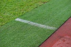 Kunstmatig spoor en gebied met groen die gras met kunstmatig gras wordt gecombineerd stock foto