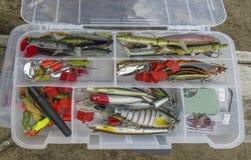 Kunstmatig vissenaas De kleurrijke Lokmiddelen van de Visserij Uitrustingen, lepels en wobblers in doos voor het vangen of visser stock afbeelding