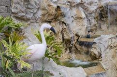 Kunstmatige flamingo dichtbij een decoratieve waterval Stock Foto's