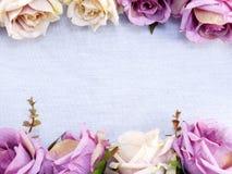 Kunstmatige purper nam bloemen op ruimte de grensachtergrond van het linnenexemplaar toe Royalty-vrije Stock Afbeeldingen