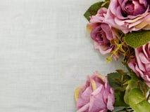 Kunstmatige purper nam bloemen op ruimte de grensachtergrond van het linnenexemplaar toe Royalty-vrije Stock Fotografie