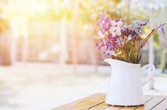 Kunstmatige purpere en witte bloemen bij witte vaas met uitstekend t stock afbeelding