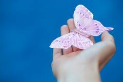 Kunstmatige vlinder op de vrouwelijke hand Stock Foto