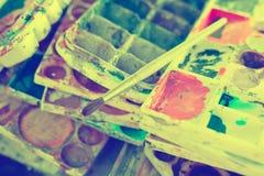 Kunstpalette mit Klecksen der Farbe und der Bürste kann herein Stockfoto