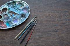 Kunstpalette und -bürsten für das Malen auf hölzernem Hintergrund Die Ansicht von der Oberseite Lizenzfreies Stockfoto