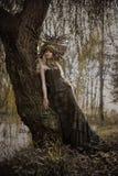 Kunstporträt einer blonden Nymphe, die in einem herbstlichen Park aufwirft stockfotos