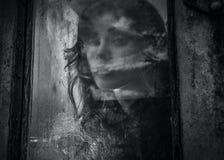 Kunstporträt einer schönen jungen gespenstischen Frau, Blicke durch Schmutz redete Fenster an. Stockbild