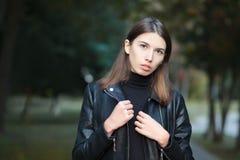 Kunstportret van het jonge vrij donkerbruine vrouw stellen in openlucht op de zwarte van het de stadspark van de leerlaag againt  Stock Afbeeldingen