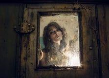 Kunstporträt einer schönen jungen gespenstischen Frau, Blicke durch Schmutz redete regnerisches Fenster an. Stockbilder