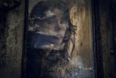 Kunstporträt einer schönen jungen gespenstischen Frau, Blicke durch Schmutz redete regnerisches Fenster an. Lizenzfreie Stockfotografie