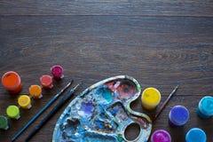 Kunstreeks, palet, verf, borstels op houten achtergrond stock foto