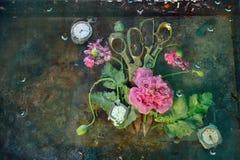 Kunststillleben mit zwei Scheren, die nahe bei umgeben durch rosa Blumen von Gebirgsmohnblumen, auf den Gläsern unter Wasser lieg Stockfotografie