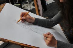 Kunststudent-Nahaufnahmehände an der Schreibtischzeichnung mit Bleistift stockbild