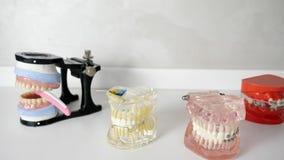 Kunsttanden met tandsteunen die op witte lijst leggen stock footage